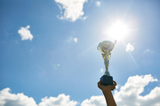 Image of childs hand holding golden cup high against background of clear blue sky in sunlight