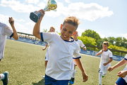 Portrait of soccer team captain running across field holding golden cup, with his teammates cheering in background