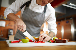 Mid section portrait of professional chef cutting vegetables in restaurant, copy space