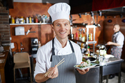 Waist up portrait of professional Asian food chef smiling at camera while posing in restaurant kitchen, copy space