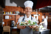 Portrait of proud professional chef presenting restaurant dish, focus on foreground