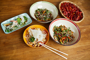 Above view background of several Asian food dishes on wooden table, copy space