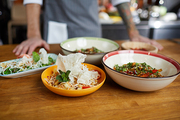 Close up of several Asian food dishes on wooden table in restaurant, copy space