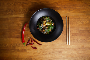 Top view background image of Asian spiced noodles on wooden table with chili peppers, copy space