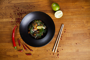 Above view background image of Asian spiced noodles on wooden table with chili peppers, copy space
