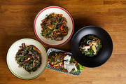 Top view of several Asian food dishes on wooden background, copy space