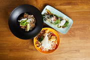Above view of several Asian food dishes on wooden background, copy space