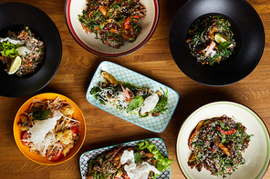 Top view closeup of several Asian food dishes on wooden background, copy space