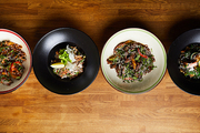 Top view of several Asian food dishes in row on wooden background, copy space