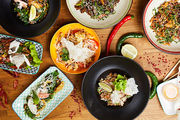 Top view close up of several Asian food dishes on wooden background, copy space