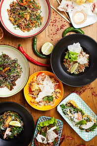 Above view composition of several Asian food dishes on wooden background, copy space