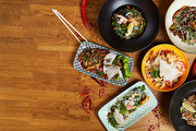 Top view composition of several Asian food dishes on wooden table, copy space