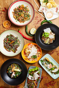 Top view background composition of several Asian food dishes on wooden table, copy space