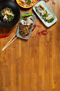 Above view background composition of several Asian food dishes on wooden table, copy space
