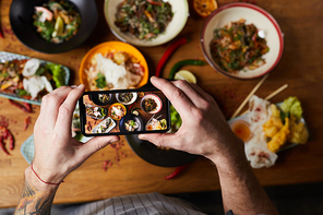 Above view closeup of unrecognizable man taking picture of Asian food dishes, copy space