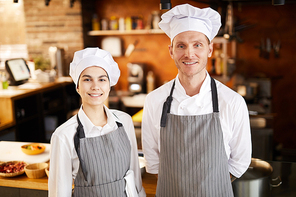Waist up portrait of two professional cooks posing in restaurant kitchen smiling at camera, copy space