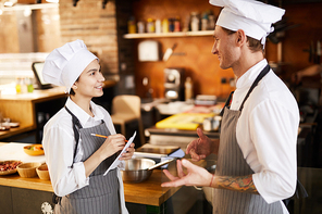 Side view portrait of two professional chefs discussing menu in restaurant, copy space