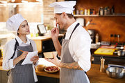 Side view portrait of two professional chefs discussing dishes while cooking in restaurant, copy space