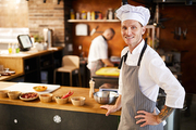 Waist up portrait of professional chef posing in restaurant kitchen nest to Asian food dishes, copy space