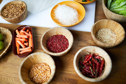 Above view background of various spices in wooden bowls on table