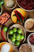 Top view background of various spices and ingredients in wooden bowls on table, copy space
