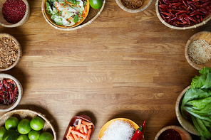 Food background of various spices standing on wooden table with empty space