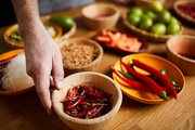 Close up of unrecognizable man holding chili peppers bowl while cooking spicy food, copy space