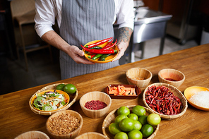 Mid section portrait of professional chef holding chili peppers and spices while cooking in restaurant kitchen, copy space