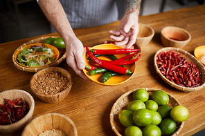 Close up of professional chef holding chili peppers and spices while cooking in restaurant kitchen, copy space
