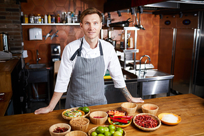 Portrit of handsome chef posing standing at table with spices, copy space
