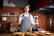 Portrit of handsome chef juggling limes standing at table with spices, copy space
