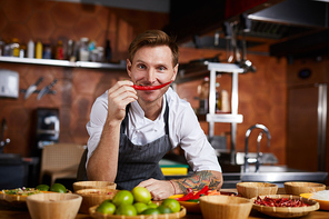 Portrait of professional chef holding red chili pepper and looking at camera, copy space