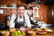 Waist up portrit of handsome chef posing in kitchen at table with spices, copy space