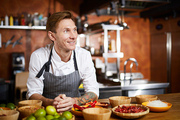 Waist up portrit of handsome chef posing in kitchen at table with spices looking away pensively, copy space