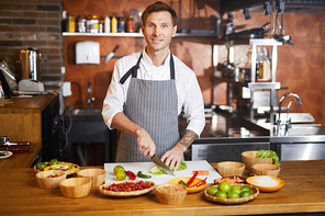 Waist up portrit of handsome chef cutting vegetables standing at table with spices, copy space