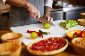 Closeup portrait of unrecognizable chef cutting vegetables while cooking spicy dish in restaurant, copy space
