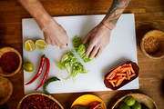 Above view portrait of unrecognizable chef cutting vegetables while cooking spicy dish in restaurant, copy space