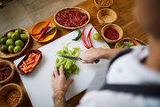High angle portrait of unrecognizable chef cutting vegetables while cooking spicy dish in restaurant, copy space
