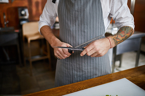 Mid section of unrecognizable chef sharpening knife in kitchen, copy space