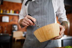 Mid section portrait of unrecognizable chef mixing something in wooden bowl with whisk