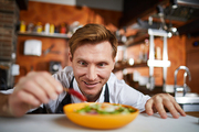 Portrait of excited chef putting hot chili pepper in salad, copy space