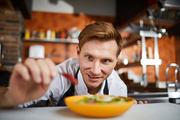 Portrait of excited male chef putting hot chili pepper in salad, copy space