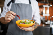 Mid section portrait of unrecognizable chef putting hot chili pepper in salad, copy space