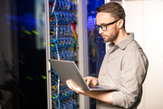 Serious thoughtful handsome young server engineer in glasses standing in database center and using laptop while troubleshooting problem with network