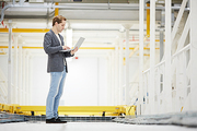 Concentrated young IT programmer in smart casual outfit standing at mining farm and using laptop while setting up server