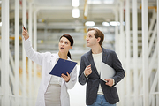 Experienced female database technician in lab coat pointing at equipment while explaining mining process to businessman