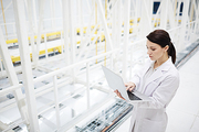 Serious busy innovation scientist in lab coat standing in modern database server and analyzing bitcoin mining operations using laptop