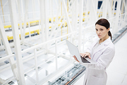Portrait of serious lady scientist in lab coat using laptop while mining crypto in database center