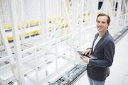 Cheerful excited young bitcoin mining expert standing in modern server room and using laptop while approving transactions