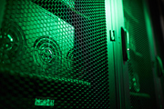 Close-up of GPU mining rigs on shelves of cabinet with ventilation doors, green lighting effect